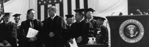 President John F. Kennedy shaking hands with the President of the University, William Friday, at the celebration of the University of North Carolina's University Day, October 12, 1961. Aycock, chancellor of the University stands on the other side of Kennedy. Henry Brandis, the dean of the Law School, stands behind and to the right of Friday. (1961)